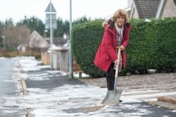Councillor Isabelle MacKenzie clearing snow and ice in winter